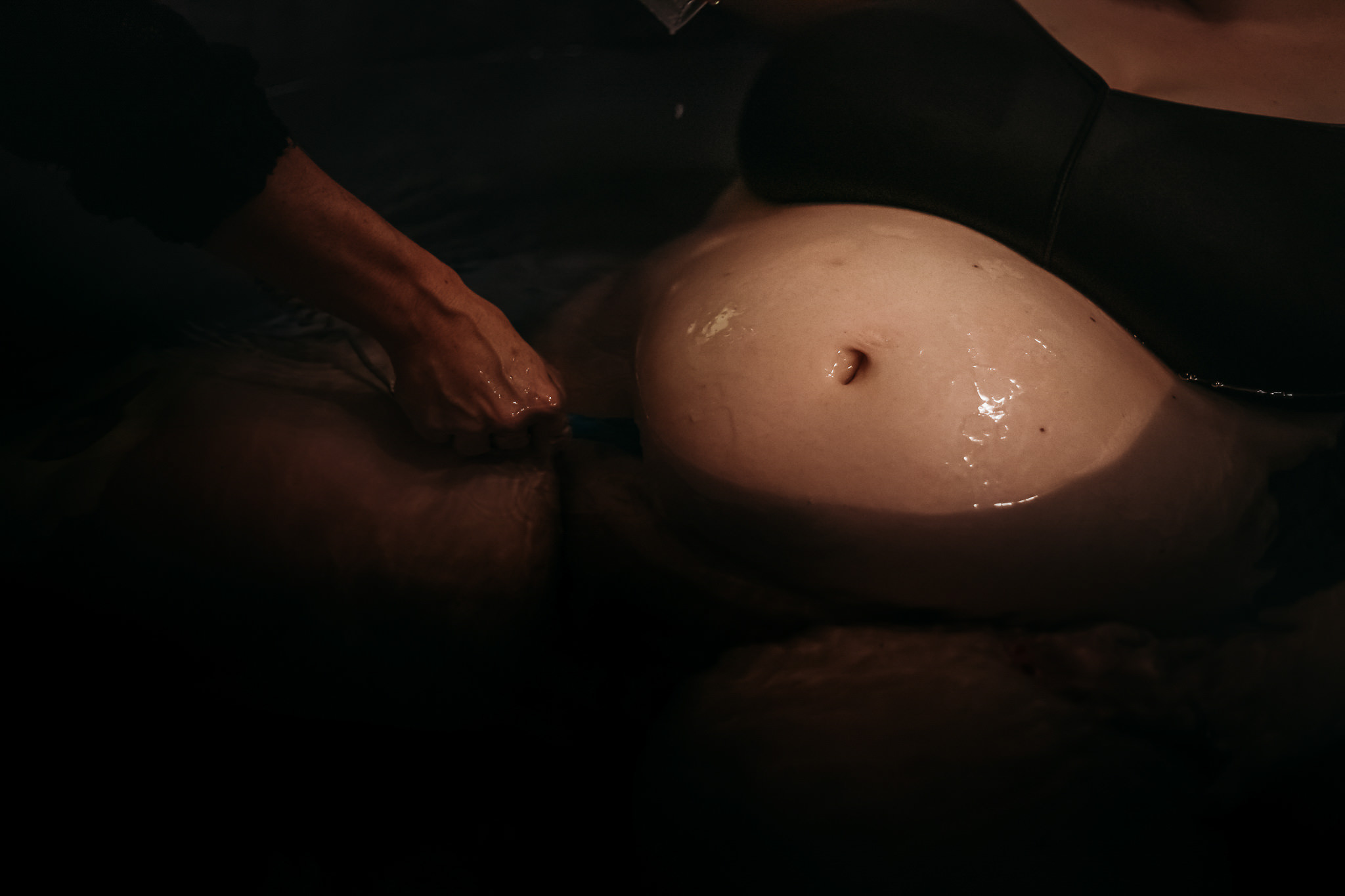 Pregnant belly in water during home birth in Abbotsford, BC