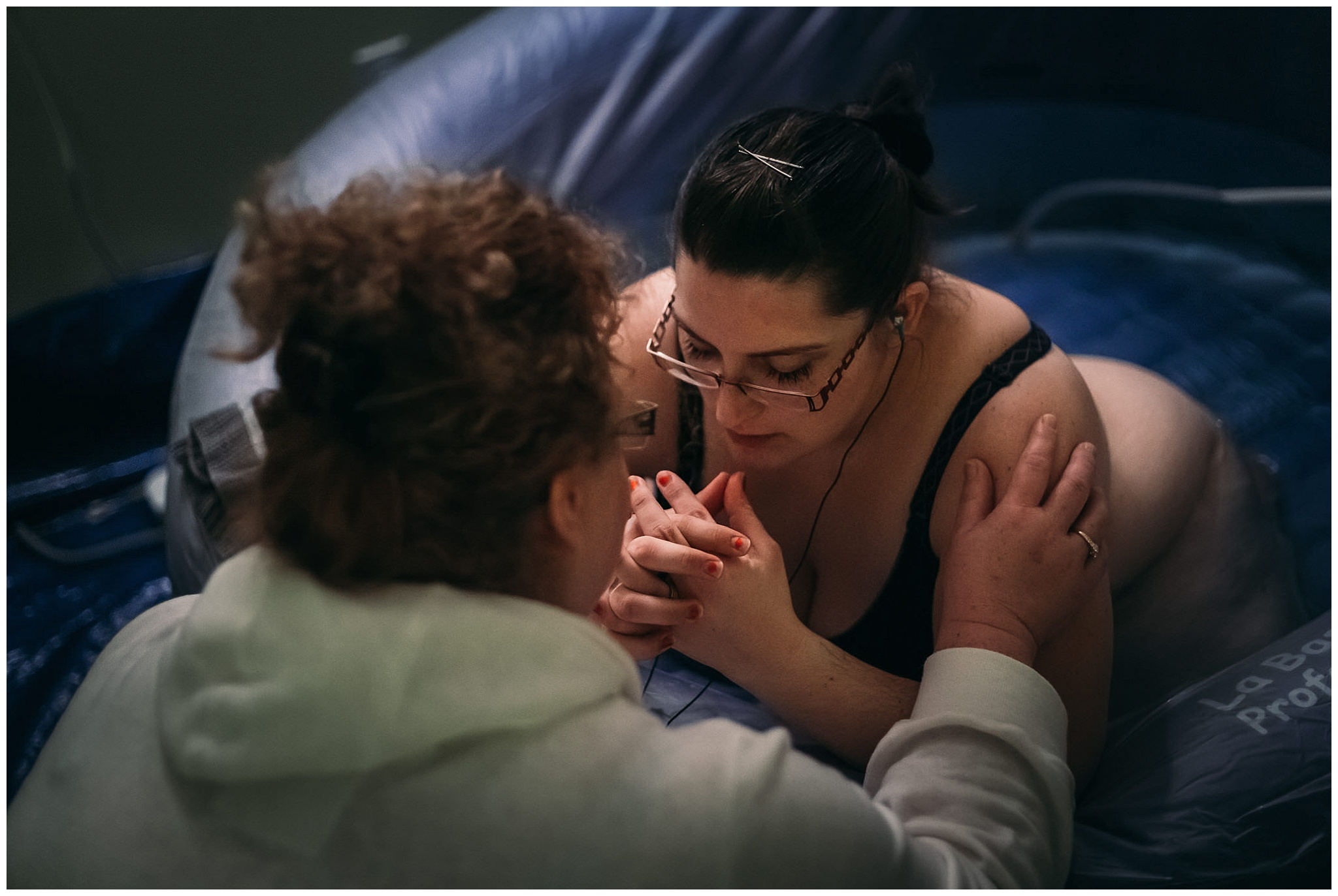 doula praying with mother while birthing newborn in birthing pool