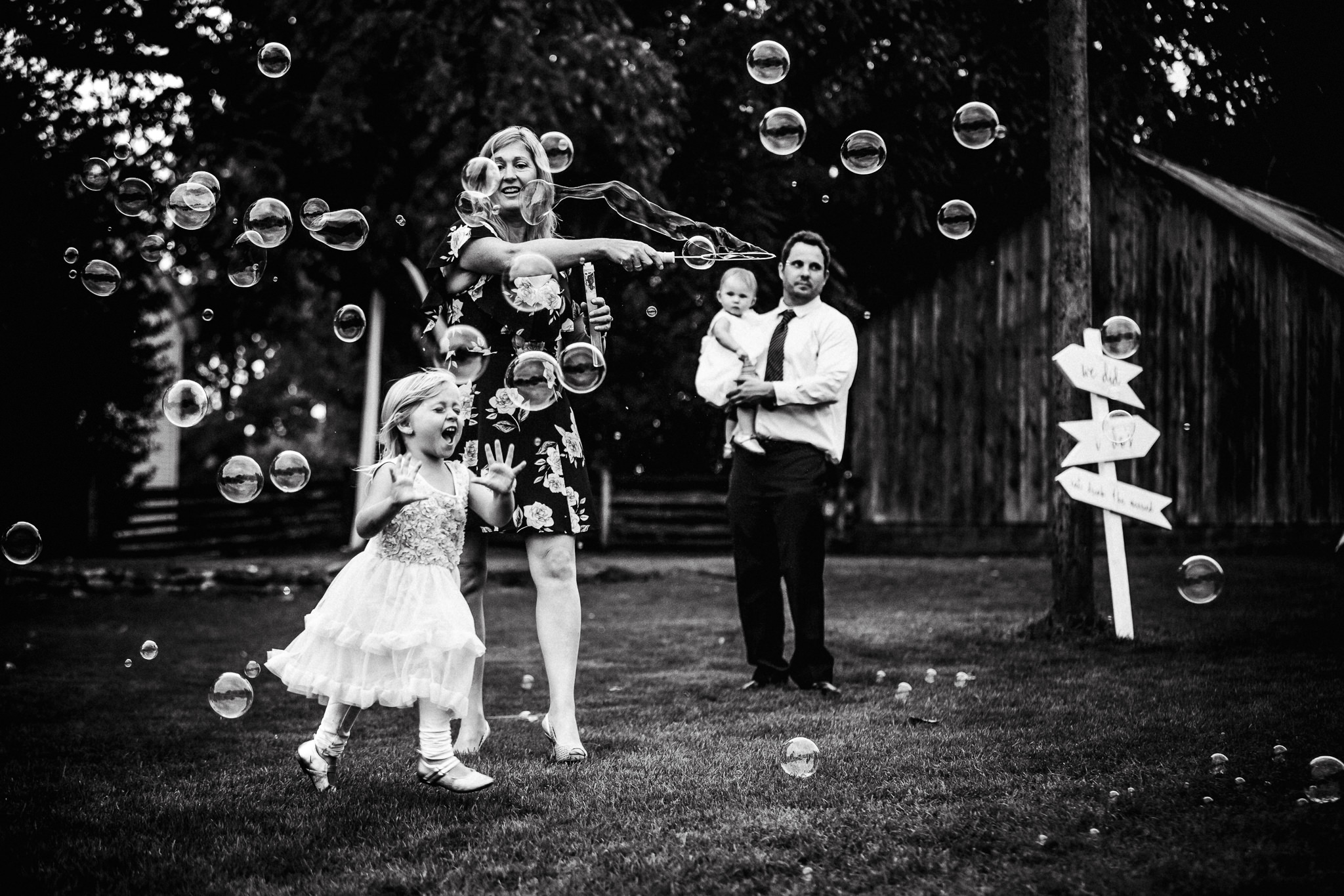 Flower girl chasing bubbles at outdoor wedding