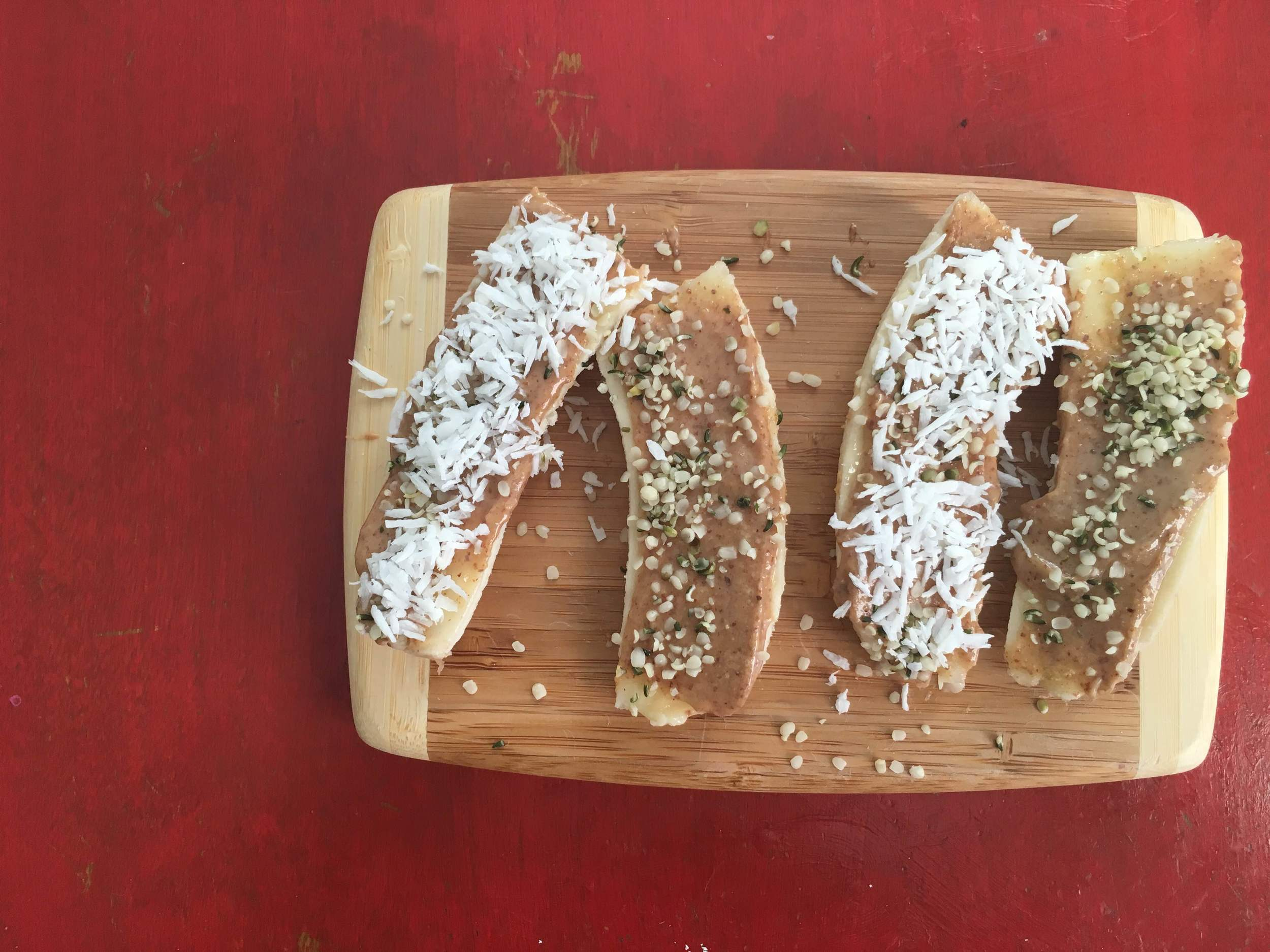 Banana Boats with almond butter, hemp seed and coconut flakes.