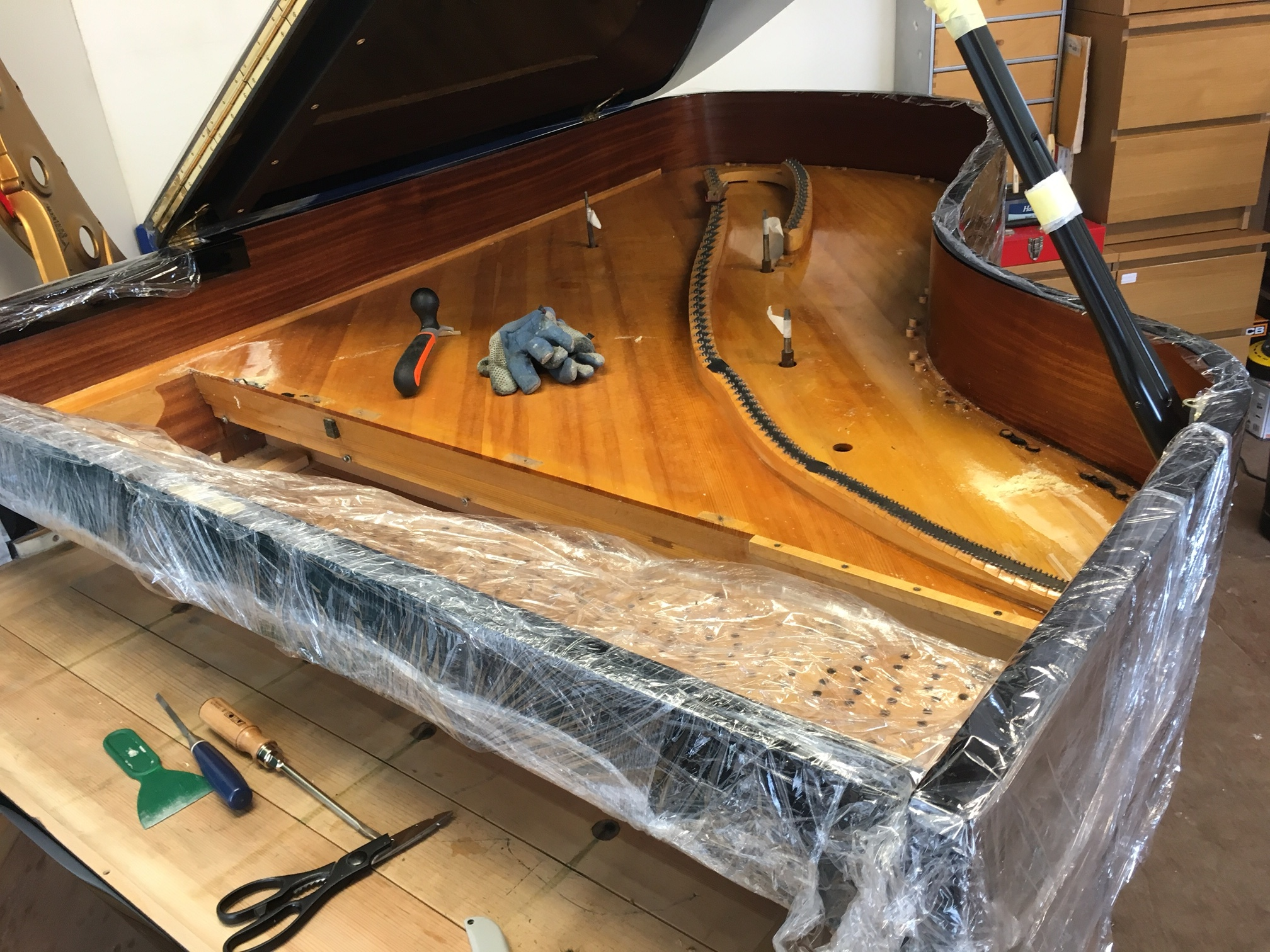 Preparing for the old soundboard varnish to be removed, prior to main lid being removed