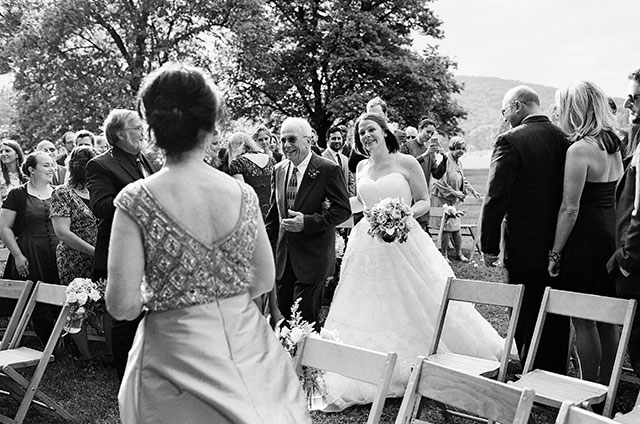 father of the bride escorts the bride down the aisle and she cries