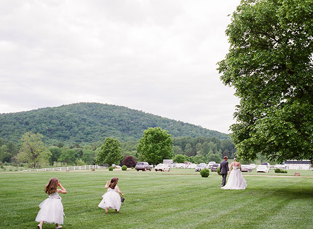 flower girls chase after couple as they process down the aisle