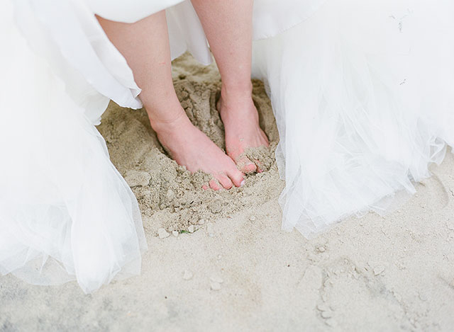 bride takes off shoes for portraits on the beach