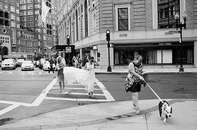 Bride crosses downtown Boston street on a windy day