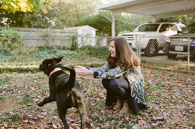 35mm color photo of girl with black lab puppy