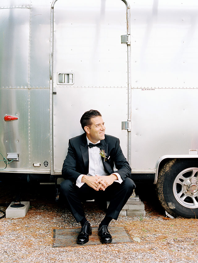 portrait of groom in front of vintage airstream trailer.