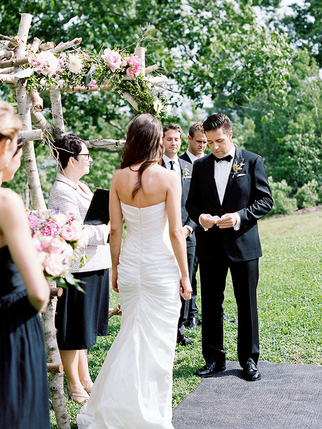 A groom reads his vows under an arbor made of wood and flowers, while the bride watches on a sunny summer day on a farm in Maine.