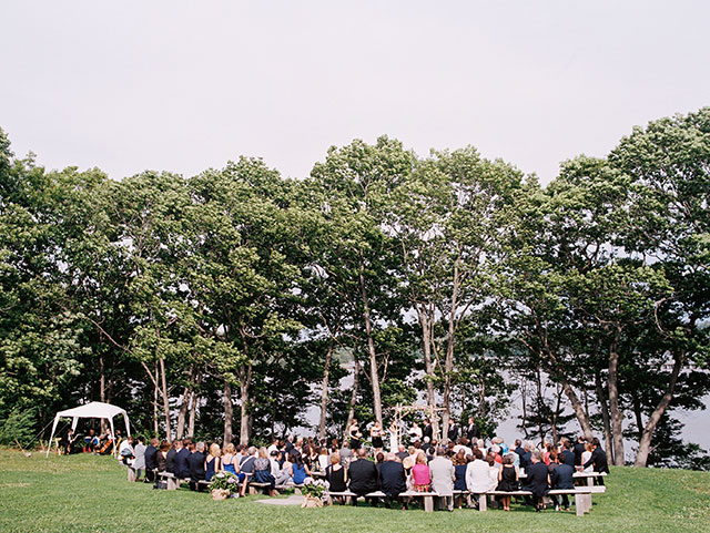 An outdoor wedding ceremony on the Casco Bay in coastal Maine, with green trees and sunshine.