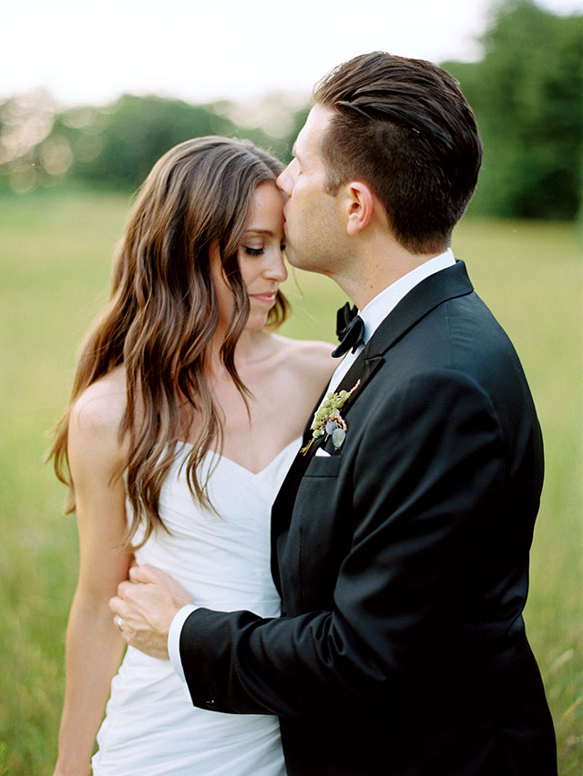 fine art film photography of groom kissing bride's forehead, shot on medium format film using a contax 645.