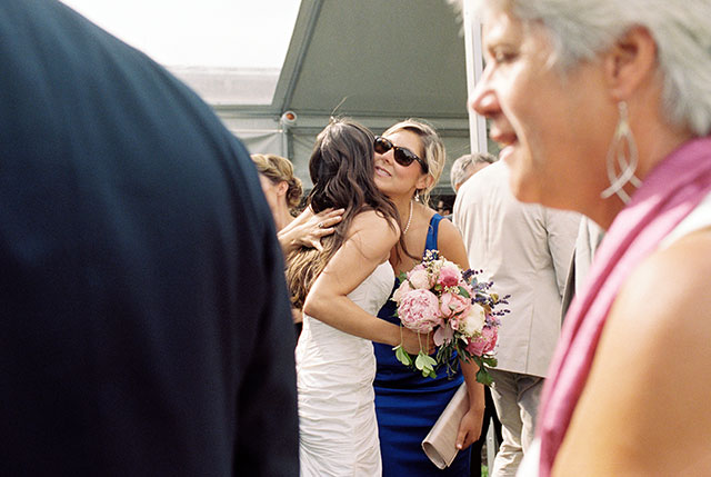 color photo of bride hugging friend who is wearing sunglasses at the outdoor cocktail hour.