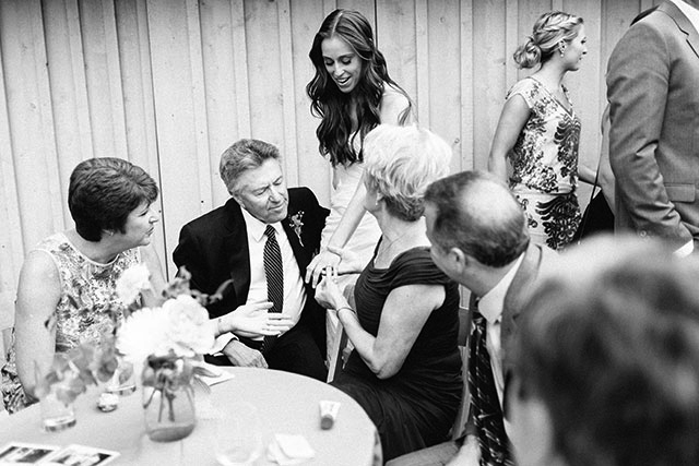 black and white film photo of bride wearing a strapless gown, showing new wedding ring to guests!