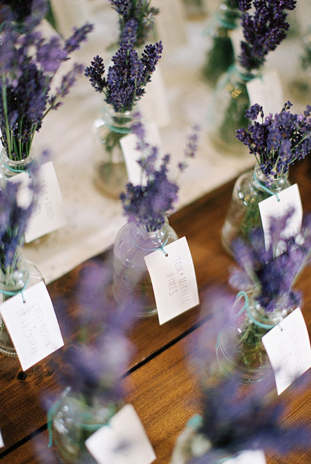 lavender wedding favors is vials with water and handwritten name tags.