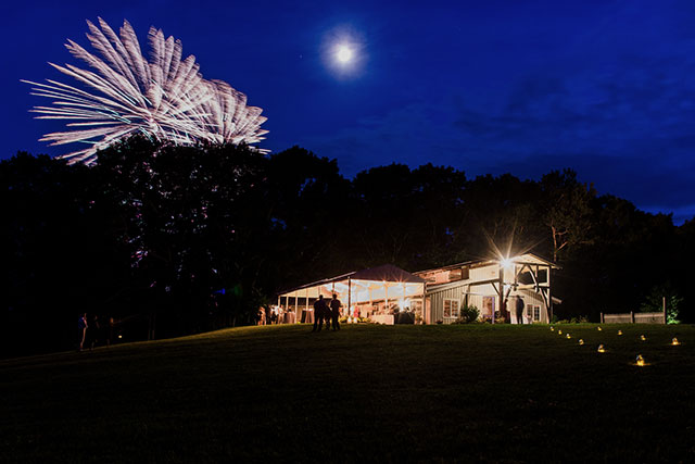 There were fireworks at this marianmade farm wedding and the barn is lit up with string lights, too.