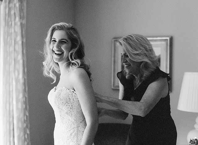 film black and white photo of bride putting on dress with mother
