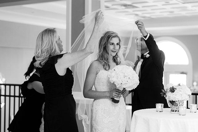 parents help bride put on veil