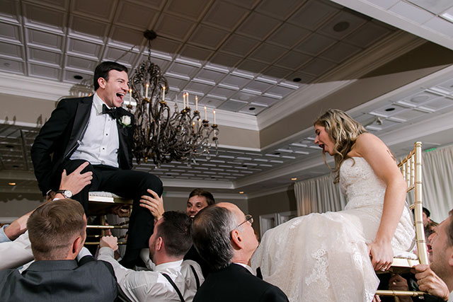 hora photos at reception of bride and groom in chairs