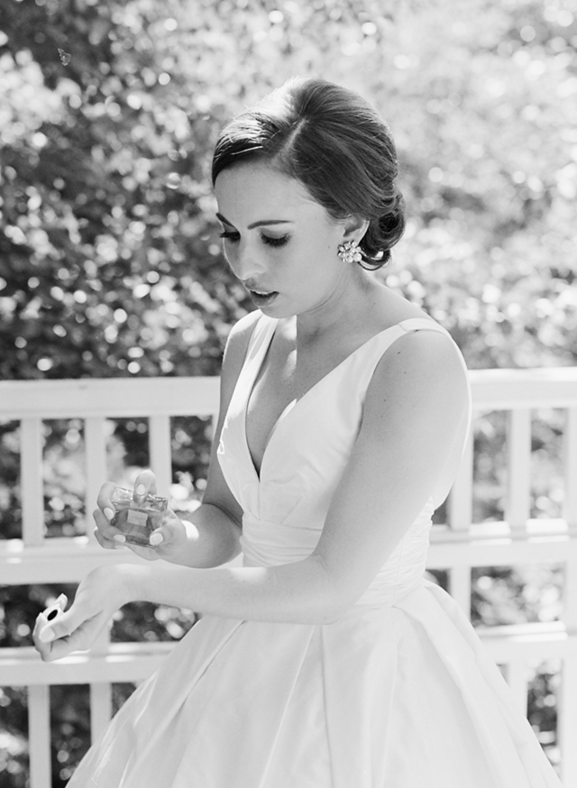 black and white film photo of bride putting on perfume