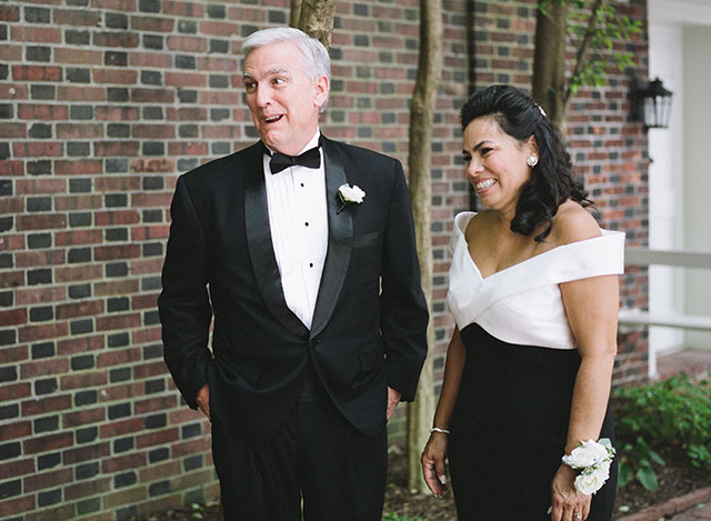 candid and sweet image of parents watching bride being photographed