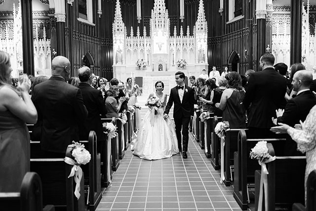 black and white image of couple walking down the aisle after being pronounced husband and wife!