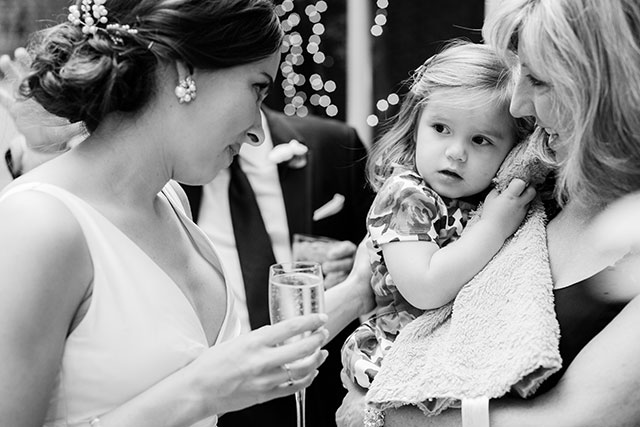 Black and white photo of bride at cocktail hour, chatting with a small girl