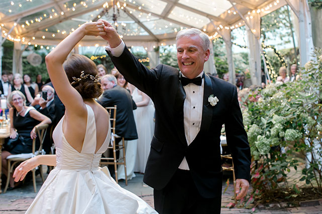 Bride and father share their first dance, father laughs