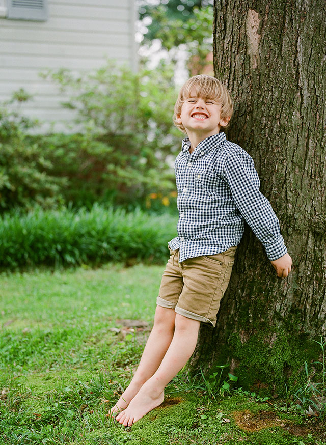 Cheesy smiles during family photo session which boy leans on tree