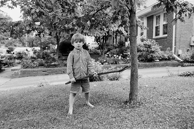 black and white film photo of boy holding stick by Sarah Der Photography