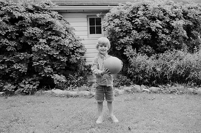 Boy holding ball in backyard on black and white Tri-X 35mm film