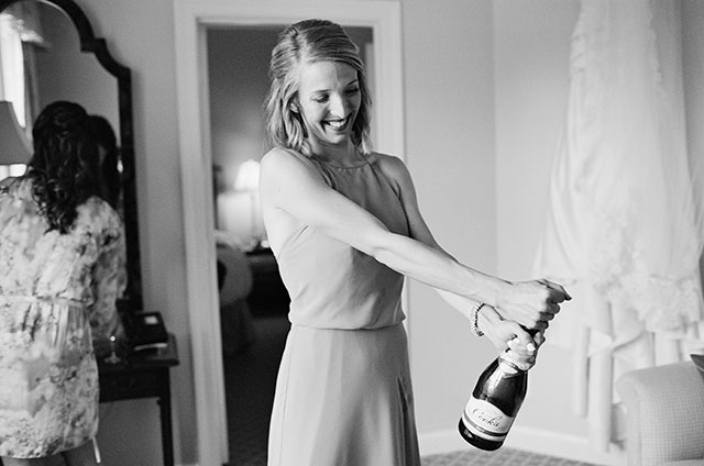 Bridesmaid pops champagne during getting ready, black and white photo on film - Sarah Der Photography