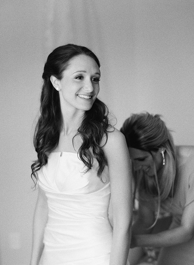 black and white film photo of bride getting into her wedding dress, smiling - Sarah Der Photography