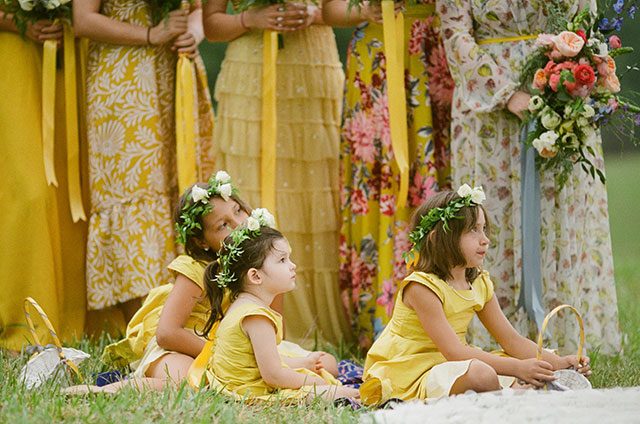 flower girls sit on rugs at front of ceremony