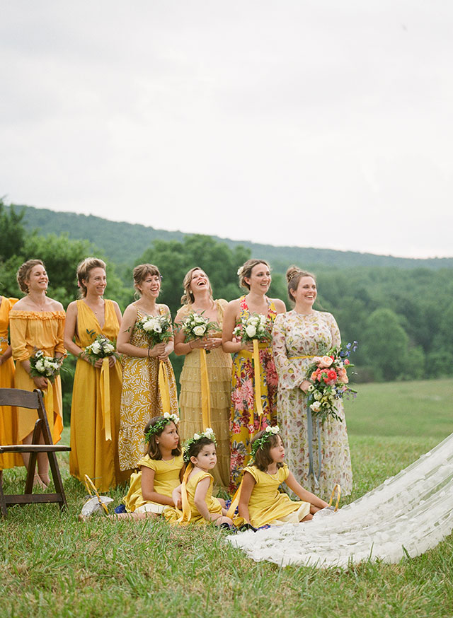 bridesmaids in mismatching yellow dresses laugh