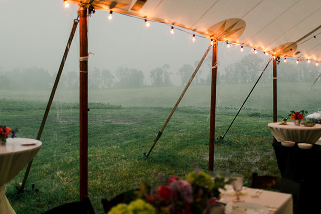 Rain pours at outdoor tent wedding reception
