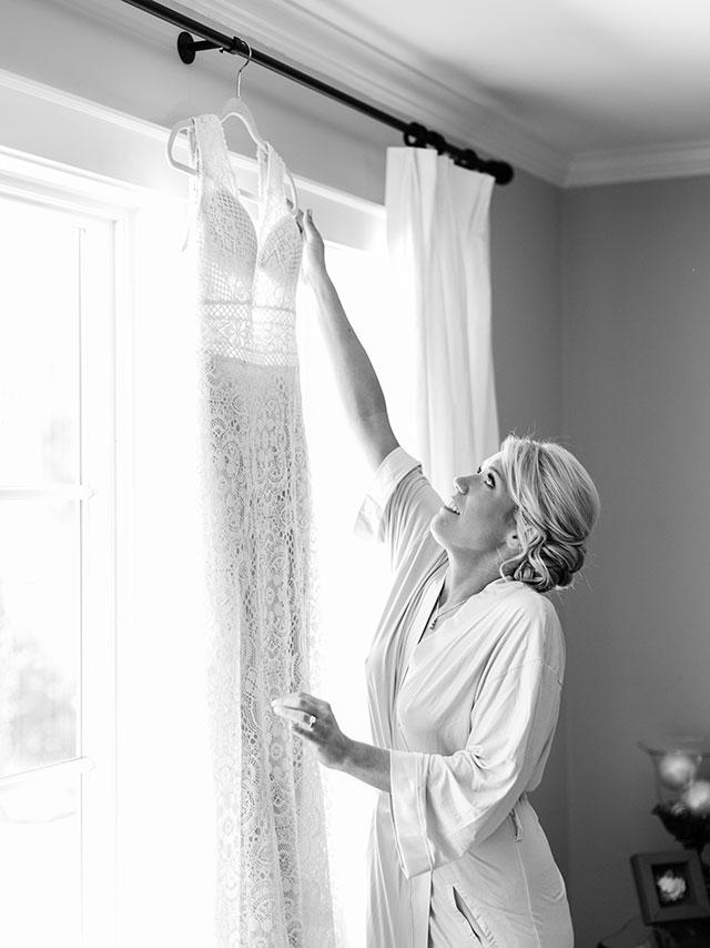 Bride reaches for wedding gown by Sarah Der