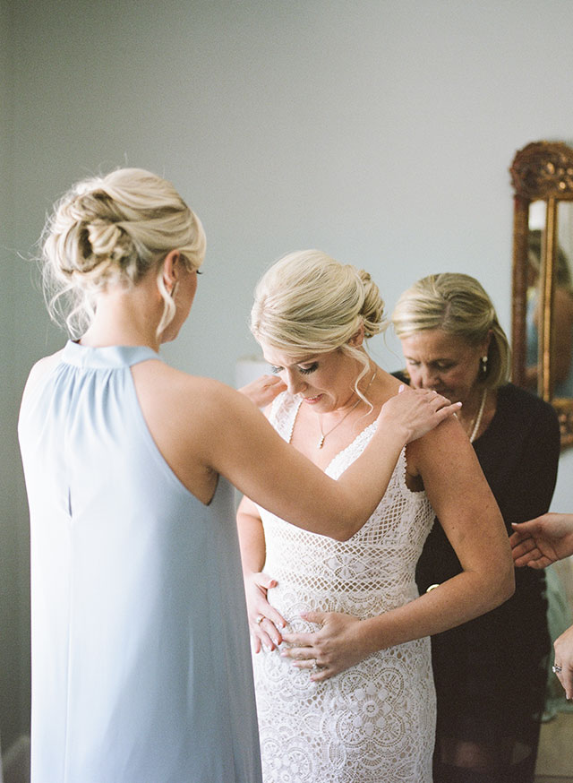 Bride puts on wedding gown, in house overlooking the cape fear country club by Sarah Der