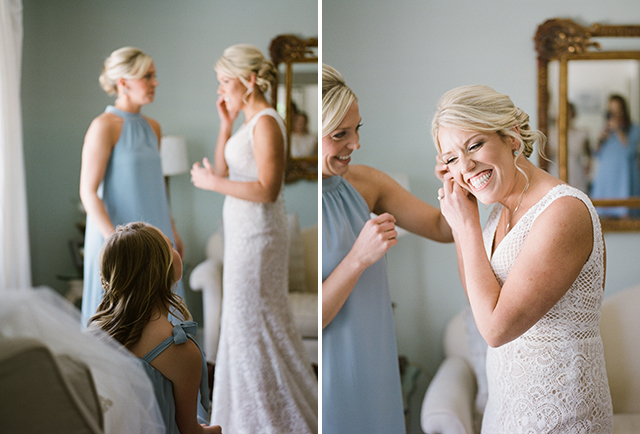 Bride smiles and puts on earrings by Sarah Der