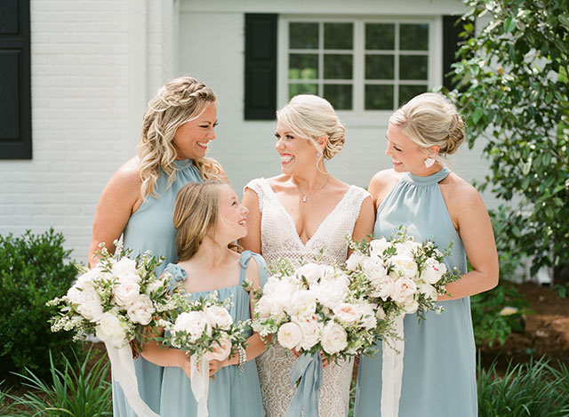 Bride and bridesmaid smile. holding floral bouquets with silk ribbons