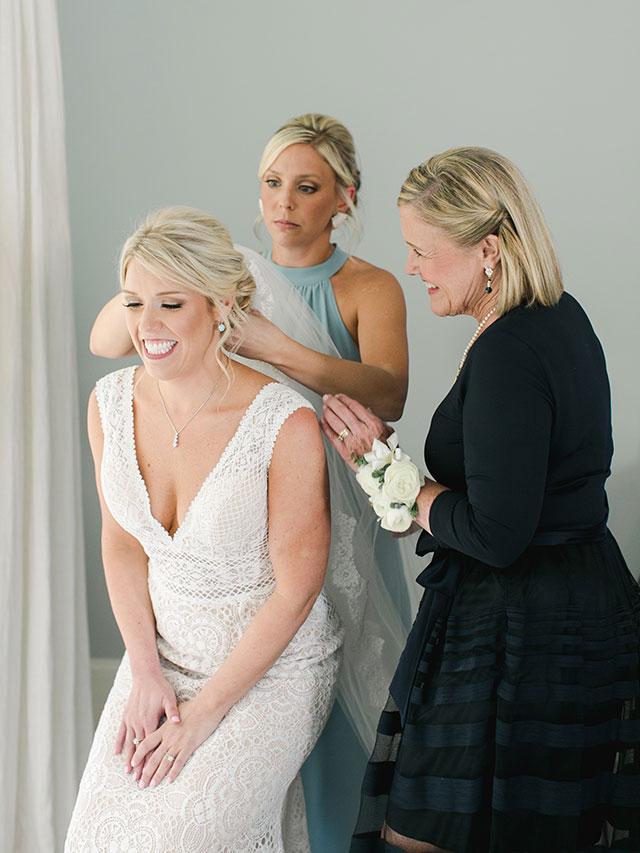 Mother puts veil on bride