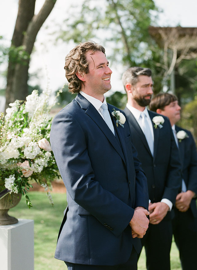 Groom sees bride and smiles as she walks down the aisle by Sarah Der