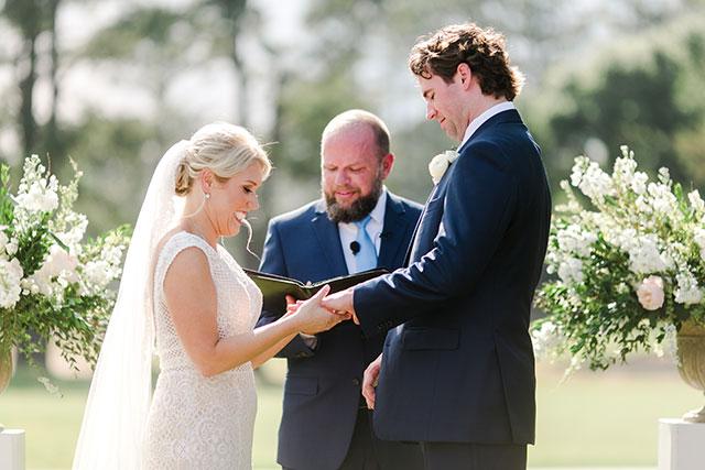 Bride puts ring on grooms finger by Sarah Der
