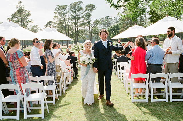 happy and joyful wedding photo of couple walking down aisle as husband and wife by Sarah Der