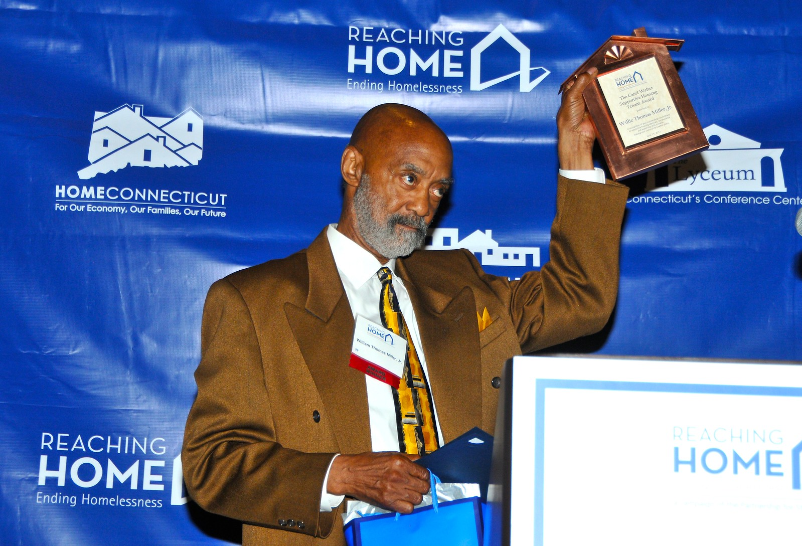 Willie Thomas Miller, proudly holding his Carol Walter Supportive Housing Tenant Award.