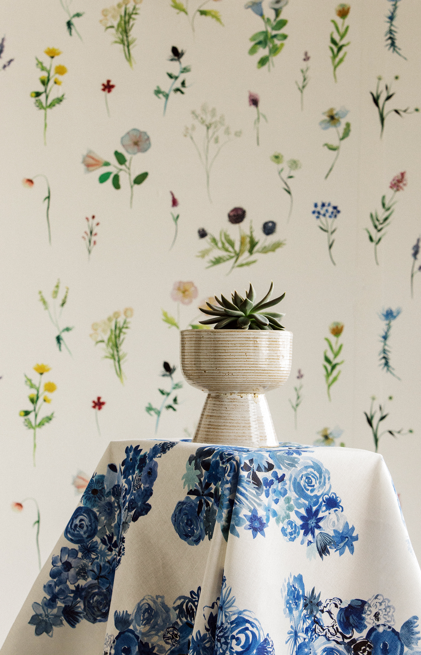 """Flora"" in 'Casbah Blue' fabric in front of ""Meadow"" in 'Heliotrope' wallpaper."