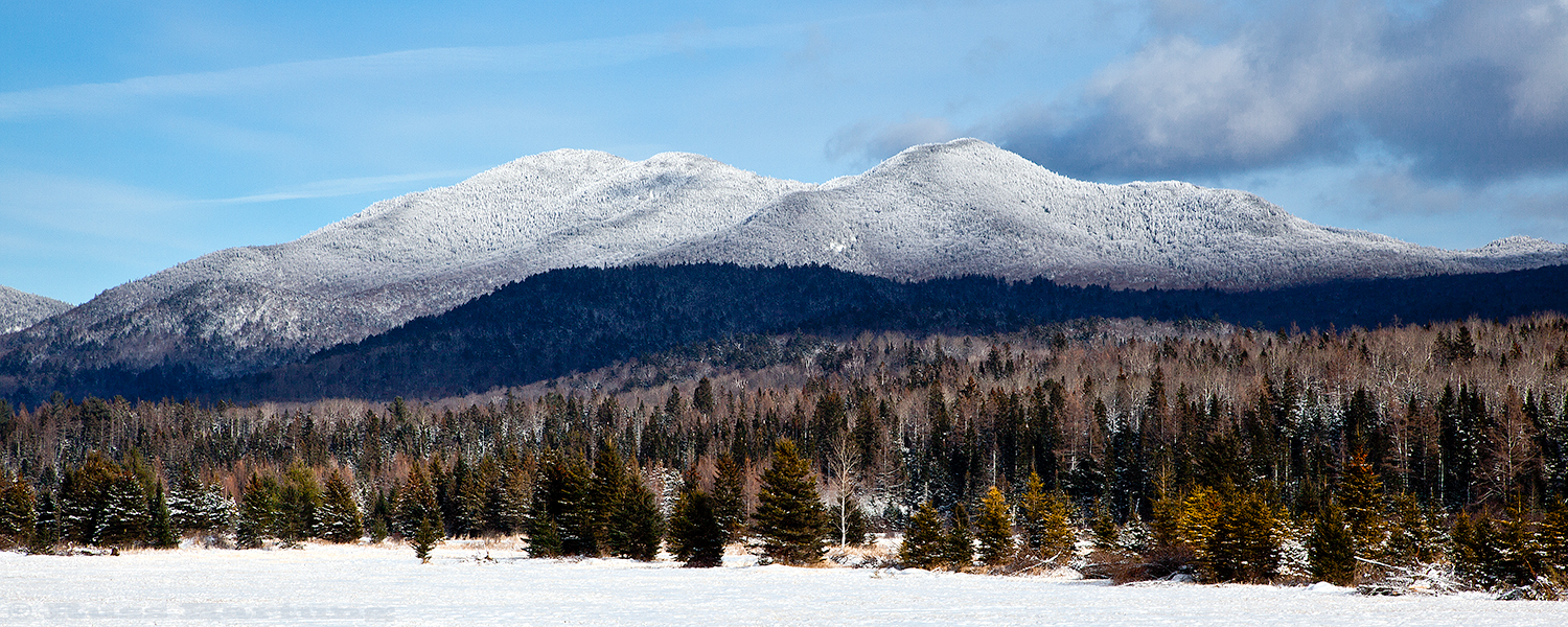 A clearing snowstorm sets off a view of the Sentinel Range near Lake Placid.
