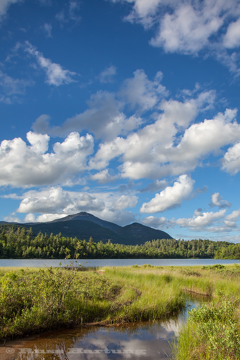 Puffy clouds over Whiteface on a bright sunny day.