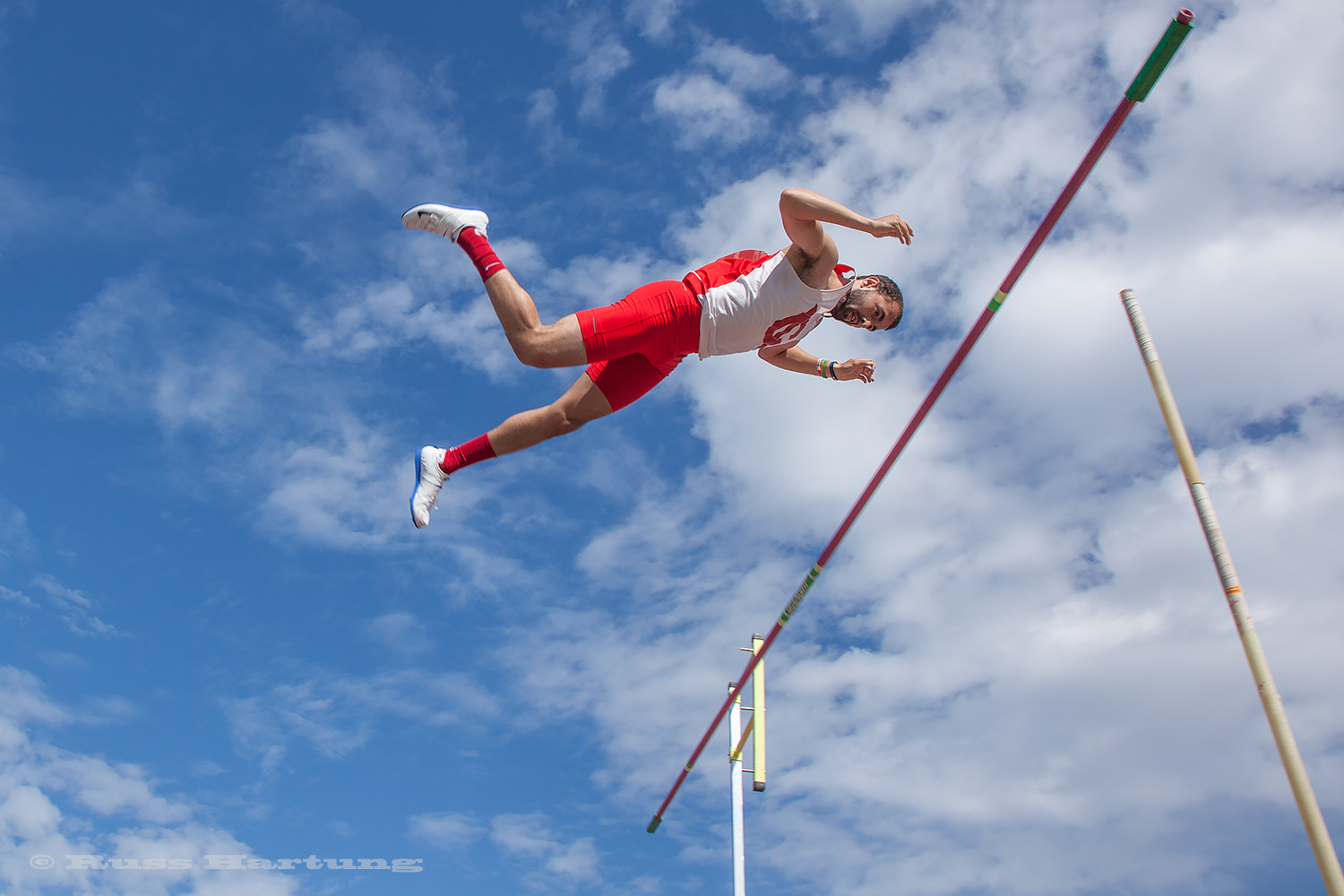 A pole vaulter seems suspended in air.