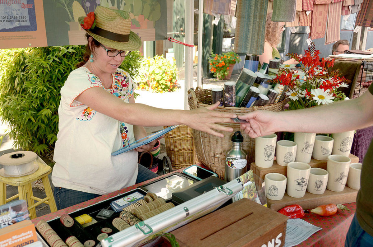 Farmers Market Coordinator Amanda Milholland hands out market tokens at the Saturday market in Port Townsend, the only one of the three markets overseen by the Jefferson County Farmers Market Association that is not being eyed for moving to a new location. (Cydney McFarland/Peninsula Daily News)