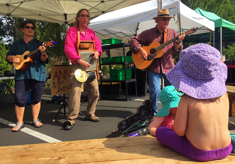 Strawberry munchers enjoy live music by Anne-O and Her Band at the Port Townsend Wednesday Farmers Market.