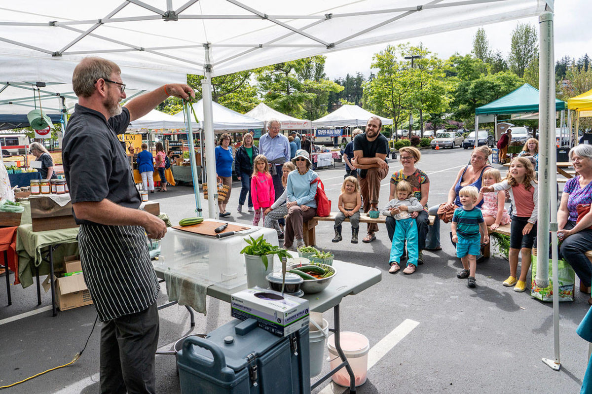 Arran Stark, executive chef for Jefferson Healthcare in Port Townsend, holds up the peel from a cucumber while giving pointers for cooking healthy foods to kids and adults at the Jefferson County Farmer's market on Wednesday. Stark demonstrated the making of a healthy dip for a crudite using fresh peas and cottage cheese as part of World Wide Breastfeeding Week with the emphasis on breast milk as the very first healthy food kids get in life. The program was sponsored by Jefferson Healthcare and Jefferson County Public Health. Photo by Steve Mullensky/for Peninsula Daily News
